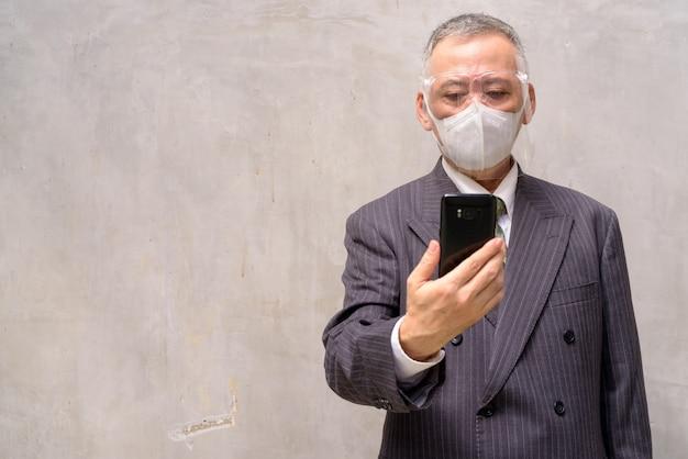 Uomo d'affari giapponese maturo con la maschera e la visiera facendo uso del telefono