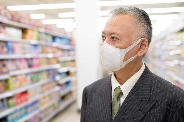Uomo d'affari giapponese maturo con la maschera che pensa e che compera con la distanza al supermercato