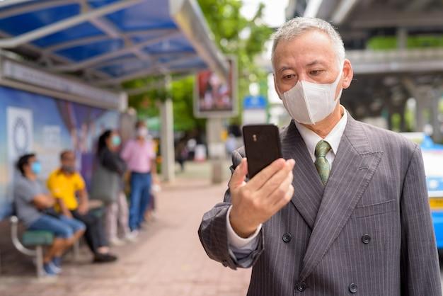 Uomo d'affari giapponese maturo con la maschera facendo uso del telefono alla fermata dell'autobus
