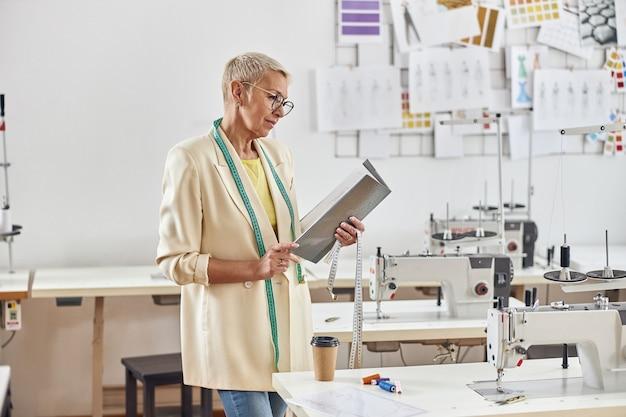 La signora matura guarda la cartella aperta in piedi nera sul posto di lavoro con la macchina da cucire