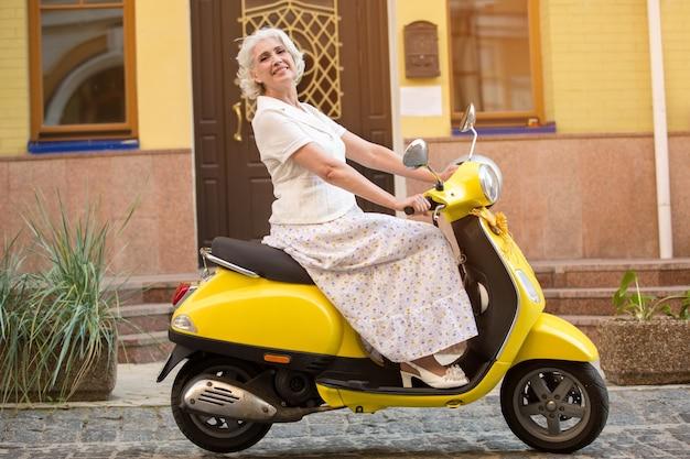 La signora matura guida uno scooter.