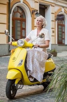Signora matura sul motorino giallo.