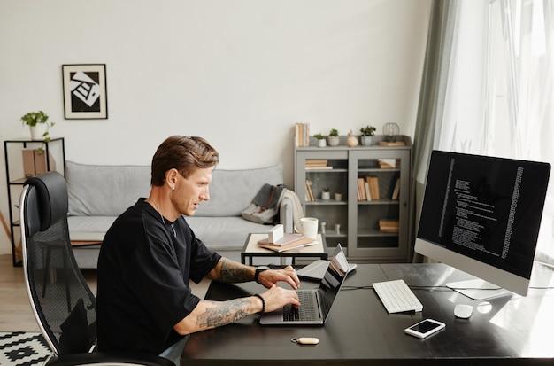 Sviluppatore maschio maturo seduto al tavolo e usando il laptop per sviluppare il programma