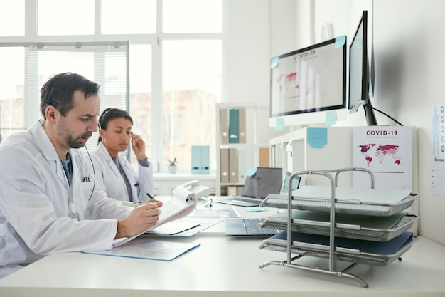 Medico maschio maturo che riempie il modulo medico al tavolo con l'infermiera seduta vicino a lui e lavorano in squadra in ufficio