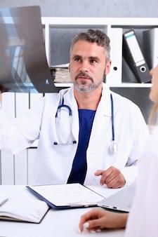 Il medico maschio maturo tiene in braccio e guarda la fotografia dei raggi x discutendola con il ritratto del paziente femminile.