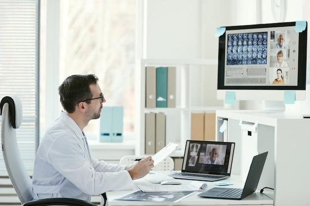 Medico maschio maturo guardando il monitor del computer e parlando con i suoi colleghi in linea in ufficio