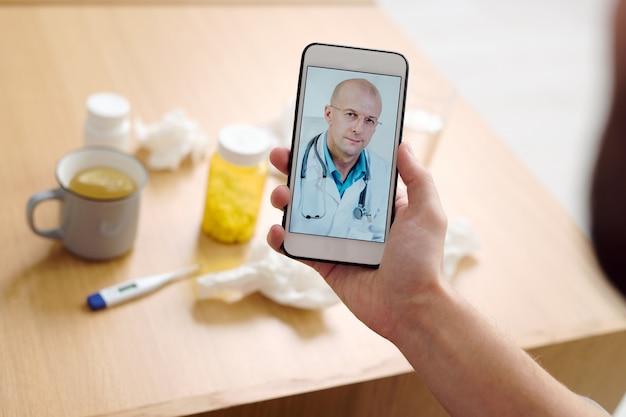 Medico maschio maturo sullo schermo dello smartphone che guarda il paziente e dà consigli medici a un giovane malato che descrive i suoi sintomi
