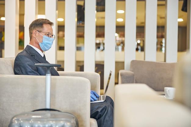Il maschio maturo in occhiali e tuta sta usando il notebook mentre è seduto in maschera di sicurezza e guanti vicino al bagaglio in aeroporto