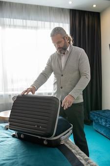 Turista maschio maturo che apre la valigia mentre è in piedi vicino al letto