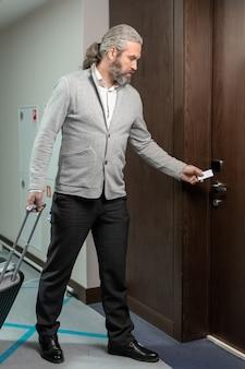 Turista maschio maturo con la valigia usando la carta bianca per aprire la porta della camera d'albergo