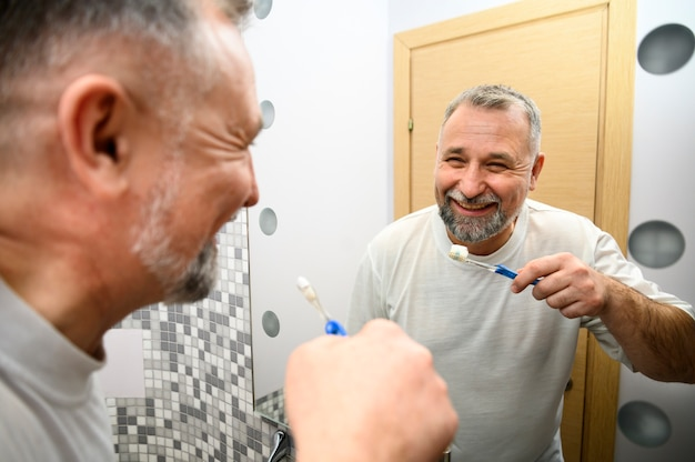 Uomo maturo, lavarsi i denti