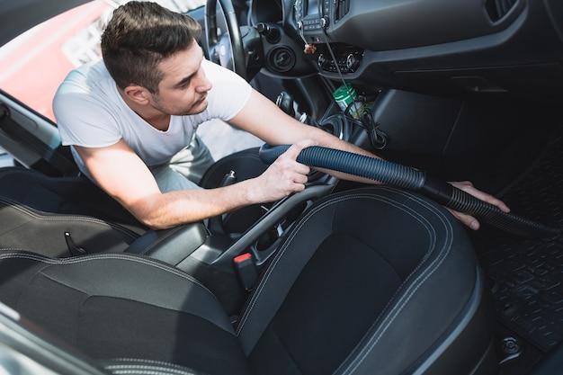 Uomo maturo che pulisce con l'aspirapolvere per interni di un'auto di lusso luxury