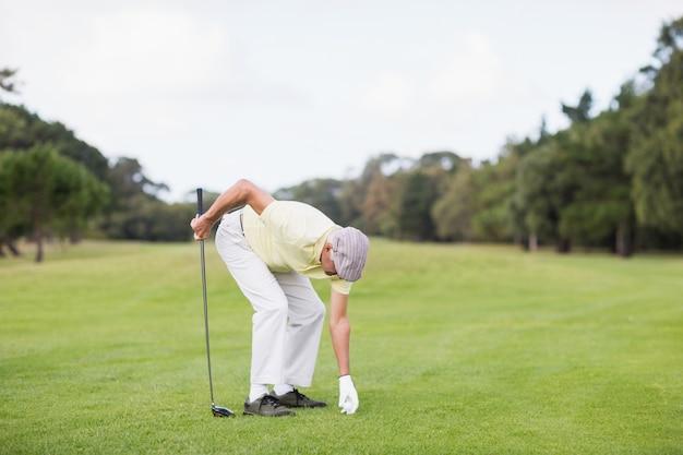 Club di golf maturo della tenuta dell'uomo mentre piegando