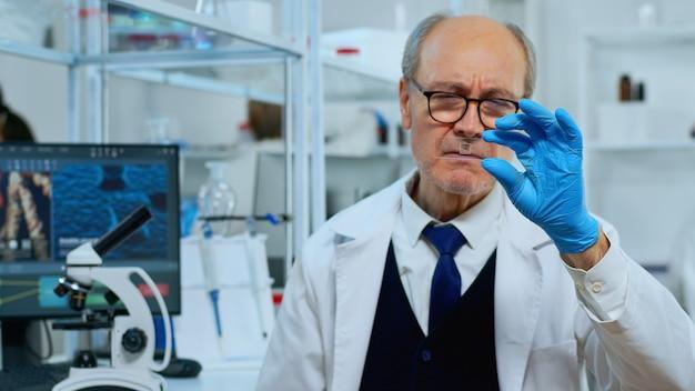 Tecnico di laboratorio uomo maturo guardando il campione di virus in un moderno laboratorio attrezzato. scienziato che lavora con vari tessuti batterici e analisi del sangue, concetto di ricerca farmaceutica per antibiotici