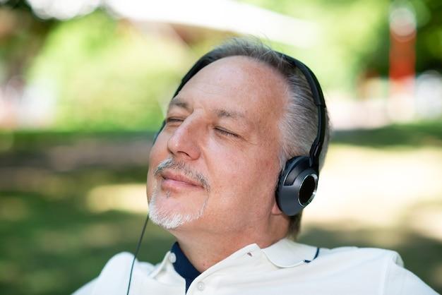 Uomo maturo che ascolta musica in un parco con gli occhi chiusi
