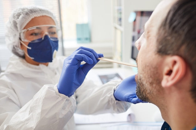 Uomo maturo che apre la bocca mentre medico in abbigliamento protettivo esaminando la sua gola durante l'esame medico all'ospedale