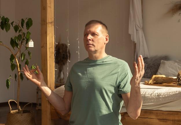 Uomo maturo che pratica yoga e medita in un'accogliente casa in stile eco nella postura di meditazione