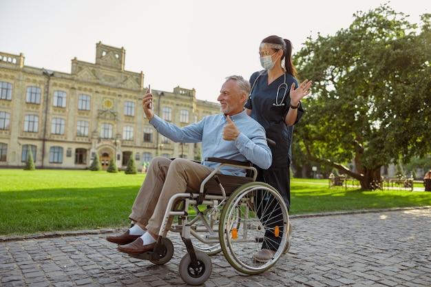 Uomo maturo che recupera un paziente in sedia a rotelle che fa una videochiamata utilizzando lo smartphone durante una passeggiata con