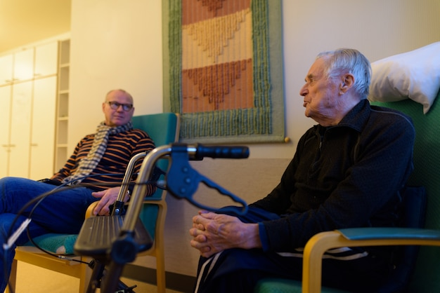 Uomo maturo e uomo anziano insieme a casa di cura a turku, in finlandia