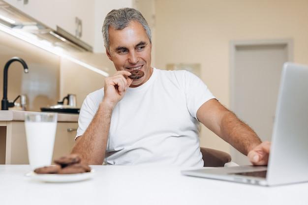 Uomo maturo seduto sulla cucina, utilizzando il suo moderno laptop grigio, guardando serie o video divertenti
