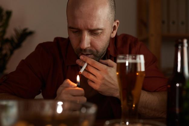 Uomo maturo seduto al tavolo fumare sigarette e bere birra