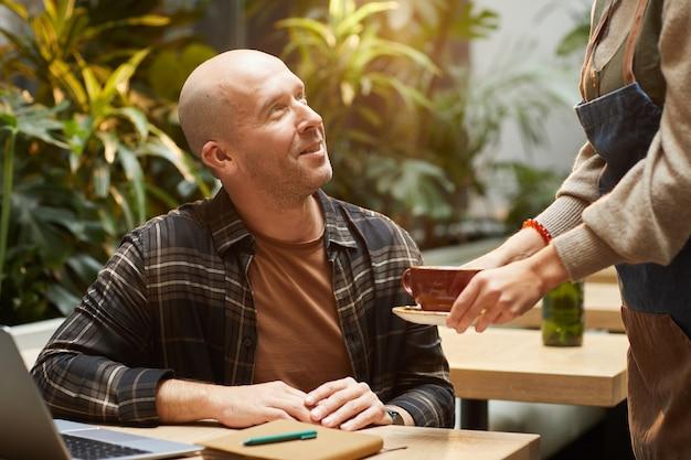 Uomo maturo seduto al tavolo con il portatile e parlando con il cameriere mentre lei gli serve il caffè nella caffetteria