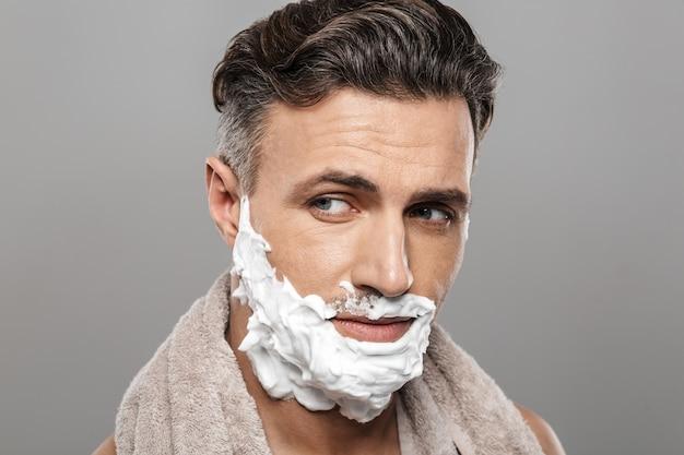 Uomo maturo in piedi isolato con crema da barba sul viso.