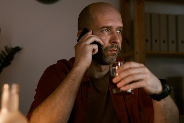 Uomo maturo che comunica sul suo telefono cellulare e che tiene vetro con alcool