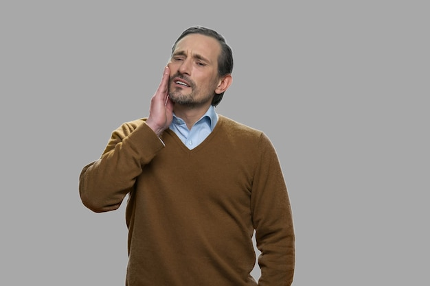 Uomo maturo che tocca la sua guancia a causa del forte mal di denti. concetto di problema dei denti.