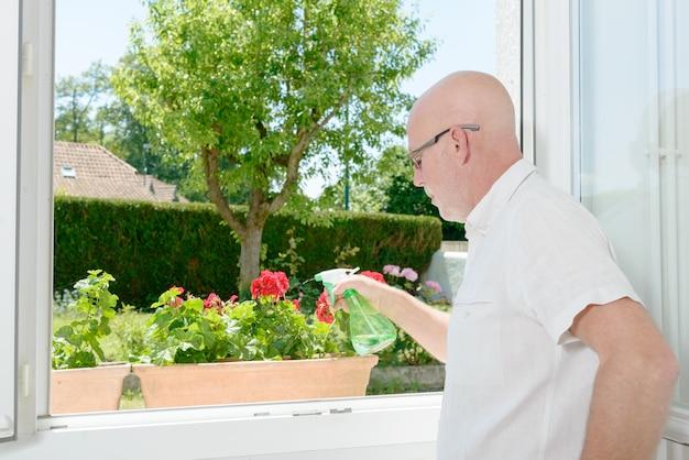Uomo maturo che innaffia i fiori