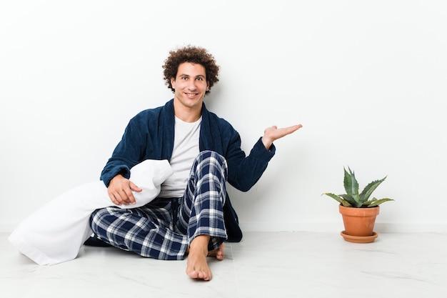 Uomo maturo che indossa il pigiama seduto sul pavimento della casa che mostra uno spazio di copia su un palmo e tenendo un'altra mano sulla vita.