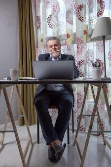 Uomo maturo con una barba che lavora a casa