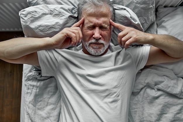 Uomo maturo con gli occhi chiusi sdraiato a letto, toccando le tempie da vicino, maschio anziano stanco che soffre di mal di testa o emicrania, malessere, insonnia, mancanza di sonno