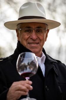 Uomo maturo con cappello brinda e beve vino in un bicchiere
