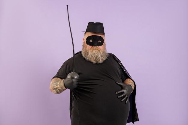L'uomo maturo con sovrappeso in costume da zorro tiene la mano su una grande pancia su sfondo viola