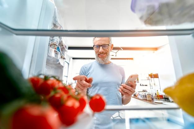 Un uomo maturo con un telefono in mano ha aperto il frigorifero per cucinare qualcosa o controllare le scorte di cibo.