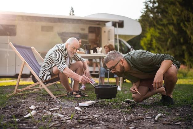 Un uomo maturo con il padre anziano che prepara il barbecue in campeggio all'aperto in roulotte per le vacanze in famiglia
