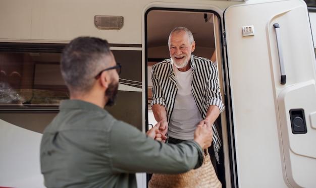 Un uomo maturo con padre anziano che disimballa in auto il viaggio di vacanza in roulotte all'aperto
