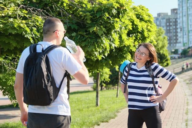 Uomo e donna maturi con gli zainhi che camminano nell'acqua potabile di conversazione del parco