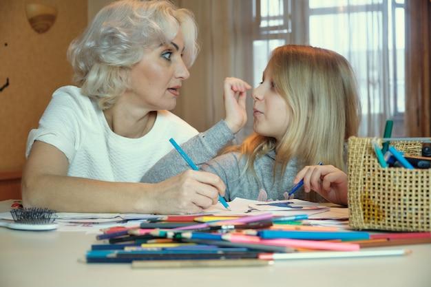 Madre matura e la sua piccola figlia che disegnano insieme, facendo i compiti a casa, fuoco selettivo