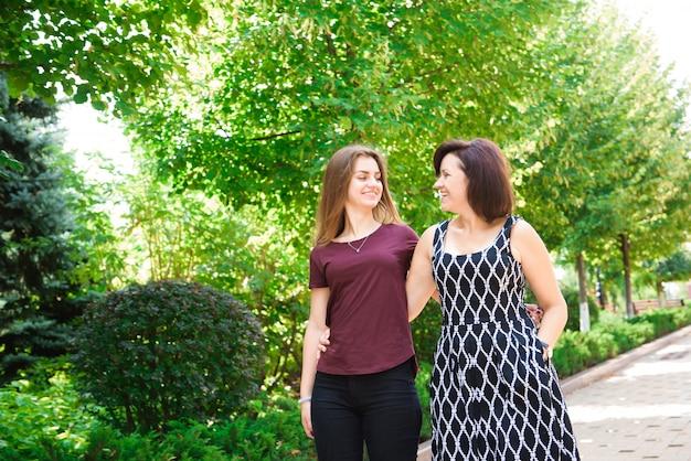 Madre matura che abbraccia con sua figlia teenager all'aperto in natura il giorno soleggiato.
