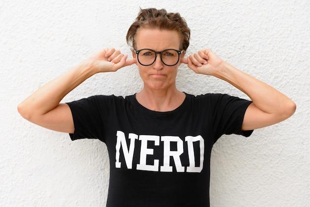 Donna matura del nerd che indossa grandi occhiali e in piedi isolato