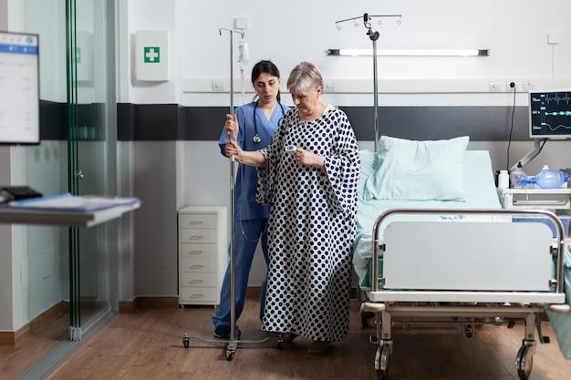 Donna malata anziana matura che ottiene medicina endovenosa dal sacchetto del gocciolamento iv. infermiera medica che aiuta il paziente a camminare attraverso la stanza d'ospedale e mostra supporto
