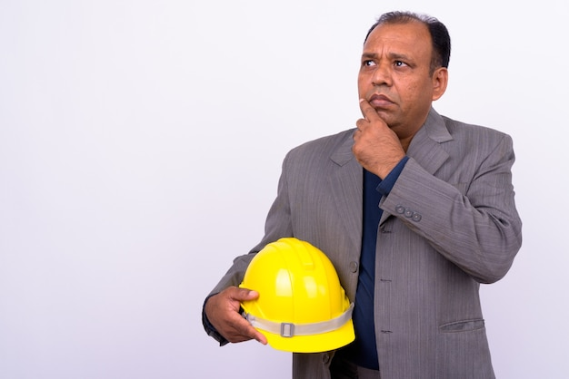 Maturo uomo d'affari indiano sovrappeso in tuta come ingegnere con elmetto protettivo su bianco