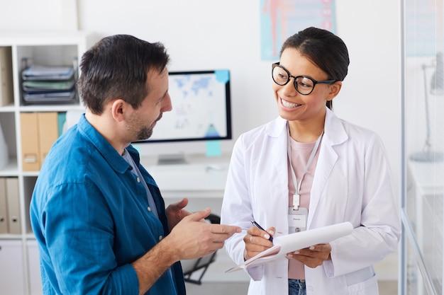 Paziente maturo che discute la prescrizione con l'infermiera mentre prende appunti nella scheda medica all'ospedale