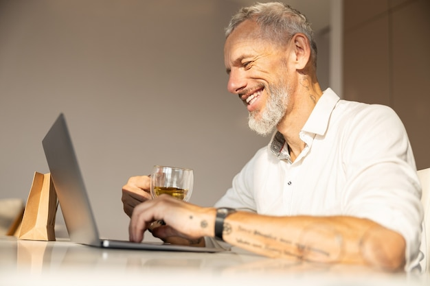 Persona matura che si gode il suo lavoro mentre consuma tè caldo