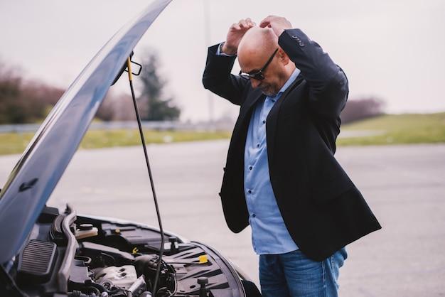L'uomo d'affari sollecitato elegante professionale maturo nel vestito sta tenendo la sua testa nella rabbia a causa del guasto del motore di automobile.