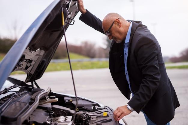 L'uomo d'affari preoccupato elegante professionale professionale maturo nel vestito sta guardando sotto il cappuccio dell'automobile che prova a capire il problema.