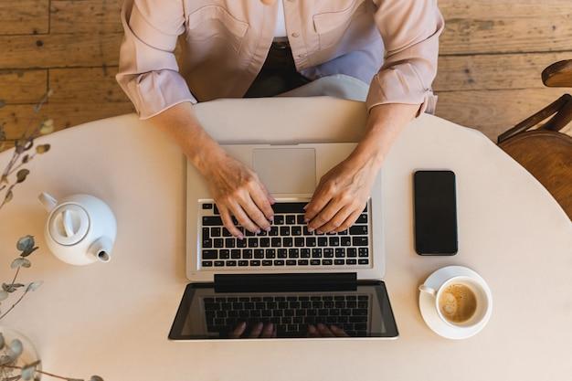 Donna anziana matura con la tazza in cucina usando il suo computer portatile. lavorare da casa in quarantena. vista dall'alto di autoisolamento di distanza sociale. schermo del cellulare.
