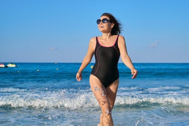 Donna matura sorridente in costume da bagno con occhiali da sole camminando lungo la spiaggia. bellezza, salute, corpo, relax per persone di mezza età. cielo blu, mare con sfondo di onde
